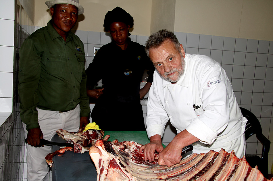 Retired chef trainer Georg Maeding shows manager and chef Fanie Hawanga and cook Wilbertina Nampala at Ondekaremba how to professionally unflesh cattle ribs